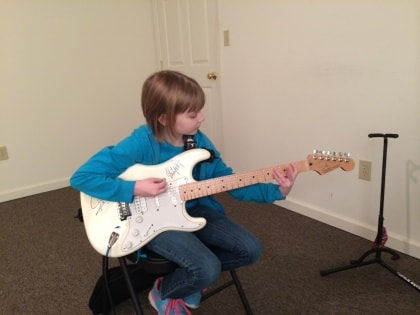 young girl learning to play guitar